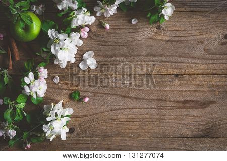 Wooden background with apple blossom flowers. Apple blossoms and green apple on rustic wooden background. Copy space for text. Post card, gift card or wedding card template. Design background
