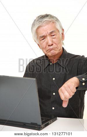 senior Japanese man using computer looking confused