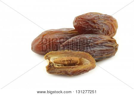 date fruit and an opened one on a white background
