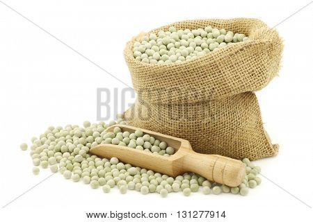 green peas in a burlap bag with a wooden scoop on a white background