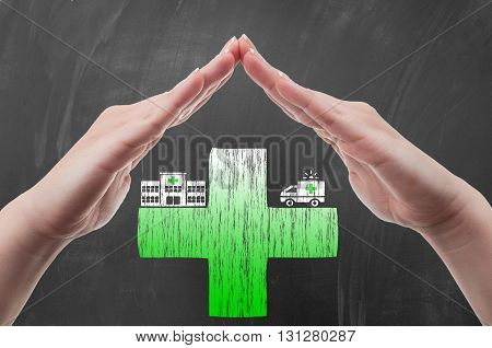 Hands protecting green cross draw on blackboard as health insurance concept