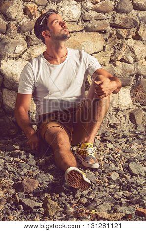 Fashion Man In White T-shirt Sitting Down On Stones