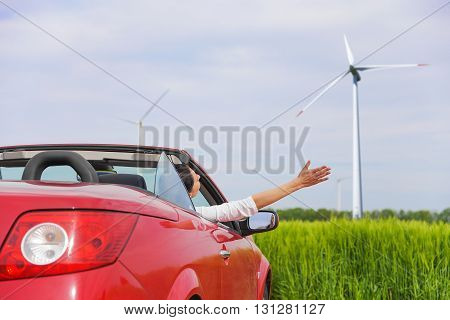 Woman in a red cabriolet in a field with wind power, raises her arms up. Travel concept.
