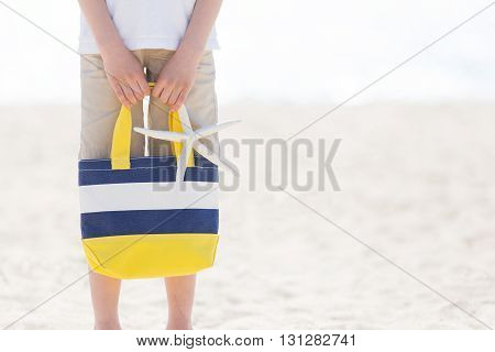 picture of boy holding colorful beach bag and starfish at the beach with no face visible with copyspace on the side vacation concept