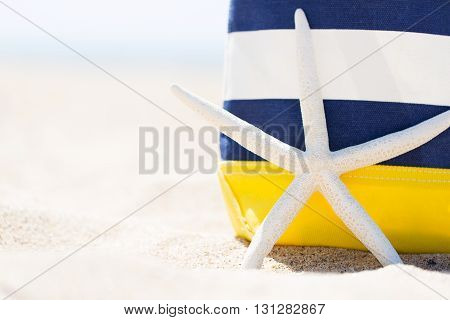 closeup picture of colorful beach bag and starfish at the beach vacation concept