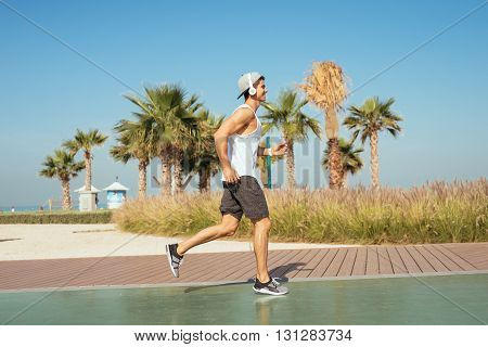Handsome man jogging outdoors on the beach.
