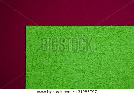 Eva foam ethylene vinyl acetate sponge plush apple green surface on red smooth background