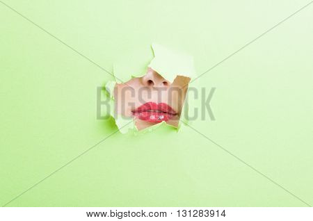 Pretty Female Mouth Wearing Lipstick Thru Ripped Paper Hole
