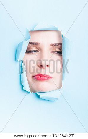 Beautiful Woman Doubt Face With Makeup Thru Torn Cardboard