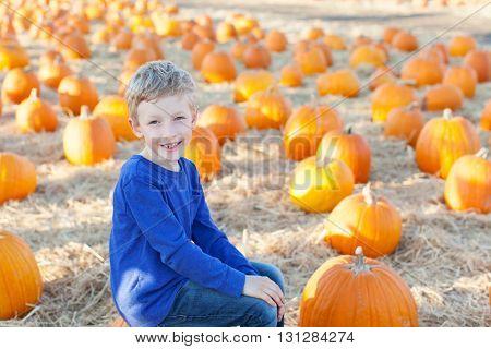 positive cheerful boy enjoying pumpkin patch at fall being playful
