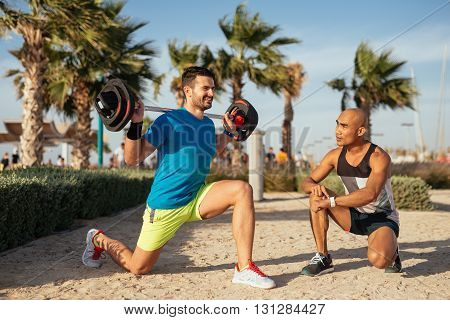 Man training on the beach with the help of personal trainer.