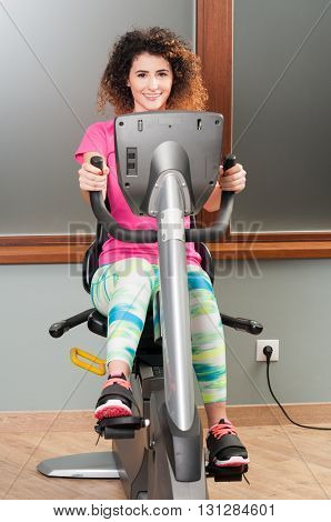 Attractive Young Female Exercising On Stationary Bike  And Smiling
