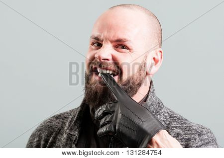 Angry Bearded Male Biting His Black Glove