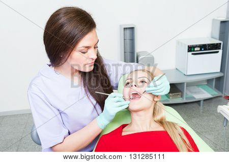 Female Patient With Open Mouth At Dentist