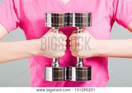 Close-up Of Woman Holding Metal Chromed Dumbbells