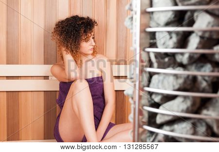 Beautiful Woman Sitting On Bench Next To Sauna Oven