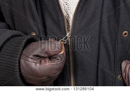 Closeup texture of open zipper jacket hold with leather gloves by man as winter outfit