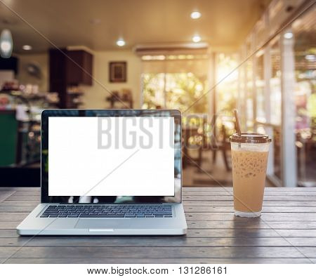 Laptop Notebook with iced coffee cup on wooden table in coffee shop