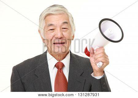 studio shot of senior Japanese businessman with megaphone