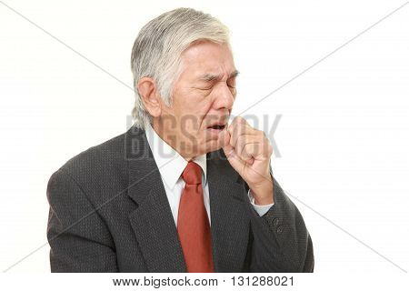 portrait of senior Japanese businessman coughing on white background