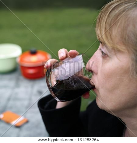 Side shot of a woman tasting red wine sitting outdoor. Focus on the wine glass blurred background