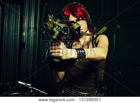 Redhead serious girl posing with ak-104 in a storage. Focus on rifle.