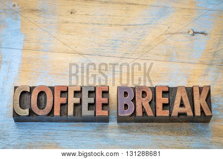 coffee break banner  - text in vintage letterpress wood type blocks stained by color inks against grunge wood with a copy space