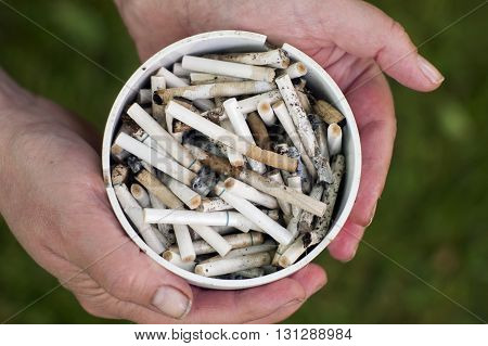 Ashtray full of cigarettes in female hands overhead detailed shot