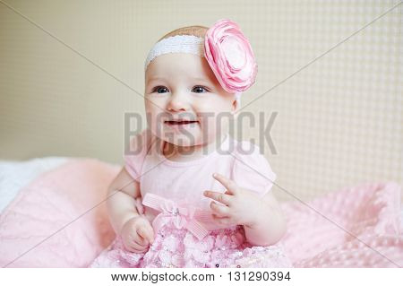 Cute beautiful baby girl sitting on a bed in pink dress and smiling.