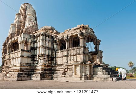KHAJURAHO, INDIA - DECEMBER 24, 2015: Indian senior in a turban worship God in front of sacred temple on December 24, 2015. UNESCO World Heritage Site Khajuraho Group of Monuments built between 950 - 1150