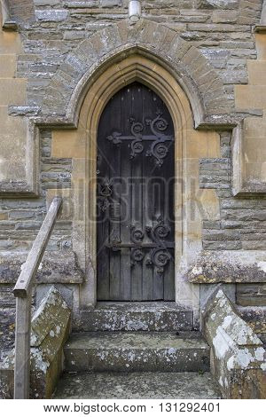 Faded old church door with wrought iron detail
