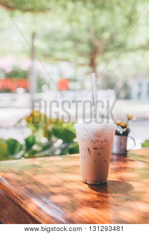 iced milk coffee in plastic cup on wooden table in tree background