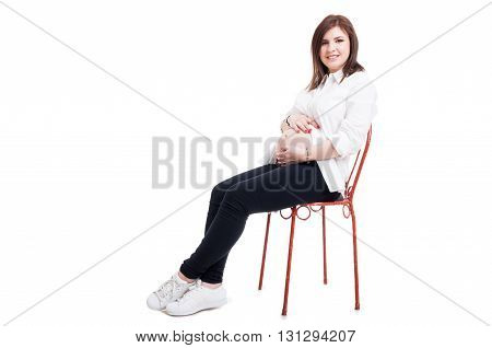 Lovely Pregnant Woman Sitting And Caressing Her Belly