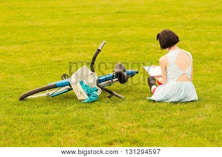 Beautiful Young Woman In Dress Sitting On Grass With A Book