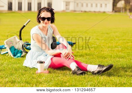 Attractive Smiling Hipster Woman In Casual Clothes Standing On Grass