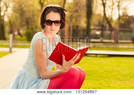 Young Beautiful Woman With Sunglasses Reading A Book Outdoor