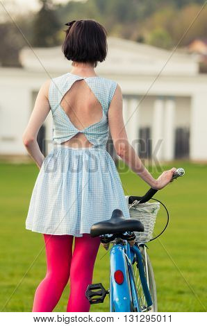 Back View Of Young Woman In Dress Walking With Bicycle