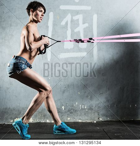 TRX - Beautiful young woman in the gym.