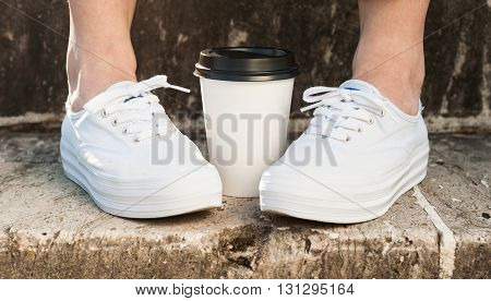 Closeup Of Female Feet Standing On Stairs Near Coffee Cup