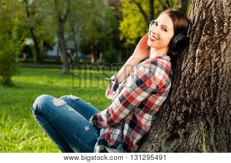 Attractive Joyful Woman Sitting Outside Under Tree And Listening Music