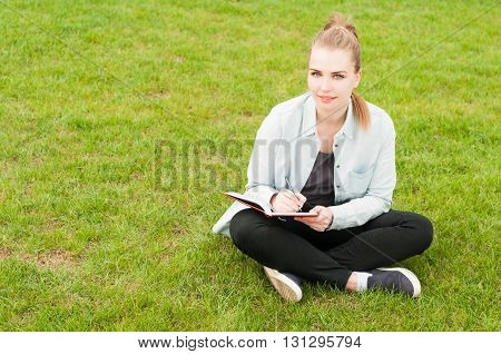 Beautiful Smiling Woman Sitting On Grass With Notebook