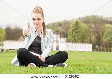Young Woman With Book Showing Thumb Up And Sitting Outdoor