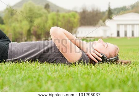 Enjoying Music In Nature Concept With Female Wearing Earphones