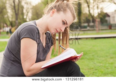 Attractive Woman Sitting Outdoor And Writes In Her Personal Journal