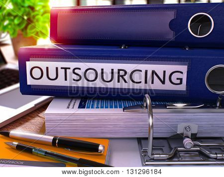 Outsourcing - Blue Ring Binder on Office Desktop with Office Supplies and Modern Laptop. Outsourcing Business Concept on Blurred Background. Outsourcing - Toned Illustration. 3D Render.