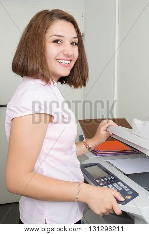 Smiling Young Secretary Using A Copy Machine