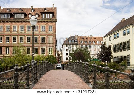 STRASBOURG, FRANCE - SEPTEMBER 09, 2010: Strasbourg's cityscape with a foot-bridge over the Ill river. Strasbourg is the capital and principal city of the Alsace region in north eastern France and is the official seat of the European Parliament.