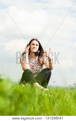 Portrait Of Cheerful Girl Thumbup And Relaxing On Meadow