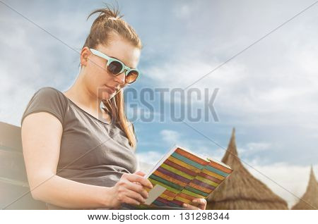 Young woman relaxing and reading a book on sunny day on the beach in her leisure time as summer recreation concept