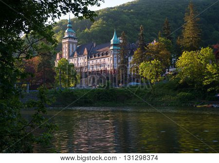 Northern front of Lillafured palace (Miskolc Hungary). Lake Hamori in foreground mountains covered with multicolored forest - background.